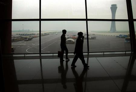 Cleaners walk past windows that look out onto the tarmac of the Beijing Capital International Airport covered in haze July 20, 2012. REUTERS/David Gray