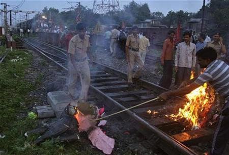 Railway policemen remove an effigy that was set on fire by demonstrators from the Samajwadi Party, a regional political party, from a railway track near Allahabad railway station September 20, 2012. REUTERS/Jitendra Prakash