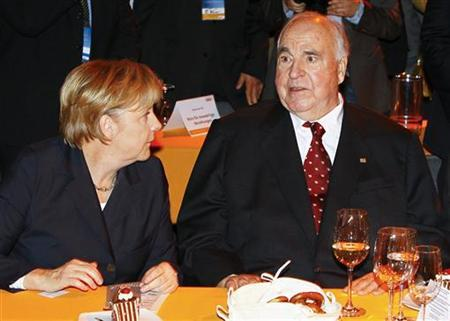 Former German Chancellor Helmut Kohl (R) speaks with Angela Merkel, his successor as Chancellor and leader of the Christian Democratic Union party CDU, during the so-called 'party evening' at the two-day CDU party congress in Karlsruhe, November 15, 2010. REUTERS/Wolfgang Rattay