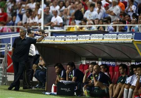 Real Madrid's coach Jose Mourinho (L) leans on his bench during their Spanish First Division soccer match against Sevilla at Ramon Sanchez Pizjuan stadium in Seville September 15, 2012. REUTERS/Marcelo del Pozo