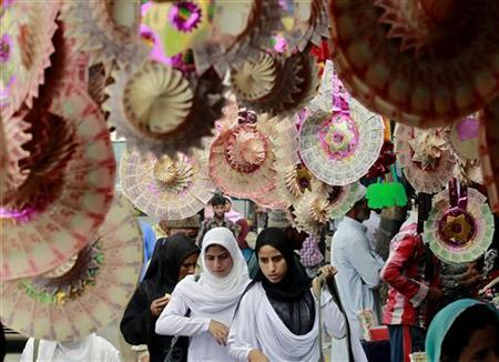 Kashmiri college girls walk under garlands made of rupee notes on display at a market in Srinagar September 3, 2012. REUTERS/Fayaz Kabli