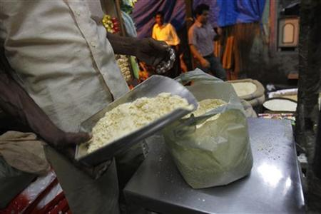 A salesman weighs chickpea flour for a customer inside a family-owned grocery store at a market in the old quarters of Delhi September 17, 2012. REUTERS/Mansi Thapliyal
