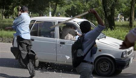 Protesters use sticks to smash the windscreen and windows of a car during an anti-America protest march in Islamabad September 20, 2012. Some 800 protesters marching towards the U.S. embassy gathered in a demonstration to condemn a film produced in the U.S. mocking the Prophet Mohammad. REUTERS/Faisal Mahmood