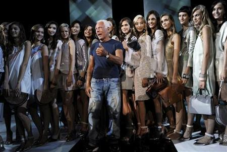 Italian designer Giorgio Armani poses with models at the end of Emporio Armani Spring/Summer 2013 collection at Milan Fashion Week September 20, 2012. REUTERS/Stefano Rellandini