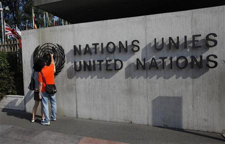 Tourists observe a logo at the United Nations European headquarters in Geneva September 11, 2012. REUTERS/Denis Balibouse