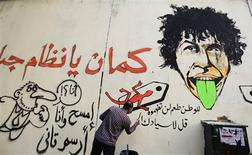 "A man redraws the graffiti along Mohamed Mahmoud street, a day after the walls were believed to be painted by government workers to cover former graffiti, in downtown Cairo September 19, 2012. The graffiti on the walls of Mohamed Mahmoud Street had existed since November, where some of the fiercest fighting between protesters and security forces took place. The graffiti in red reads: ""tell your boss that our country has a special taste for us."" The words in black (L) read: ""If you erase I will write it again."" and the words on the bottom right call the police and the country's system cowards. REUTERS/Mohamed Abd El Ghany"