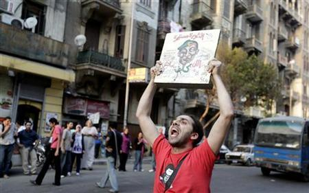 A protester shouts against the erasure of graffiti along Mohamed Mahmoud street as he holds a placard reading ''the revolution is being continued'' in Cairo September 19, 2012. REUTERS/Mohamed Abd El Ghany