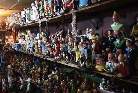 Shelves crammed with figurines from the comic strip Tintin are displayed at the workshop of Congolese artist Auguy Kakese in Kinshasa September 18, 2012. Kakese has made a career out of carving thousands of Tintin souvenirs for westerners visiting Congo. Tintin's relationship with Congo dates back to 1930 when his creator Georges Remi - better-known by his pen name Herge - first wrote ''Tintin in the Congo'', in which the intrepid reporter and his little white dog Snowy tackle wild animals, hunters, diamond smugglers and warlike local chieftains. REUTERS/Jonny Hogg