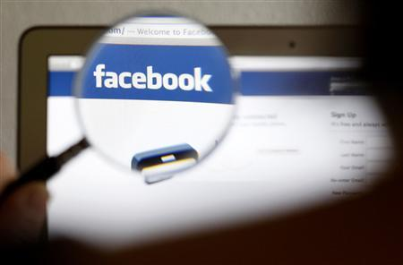 A Facebook logo on a computer screen is seen through a magnifying glass in Bern in this file photo illustration taken May 19, 2012. Facebook Inc said it will start charging businesses to run Offers on its social network, turning a previously free service into a potential revenue generator at a time when Wall Street is demanding new sources of growth and profit from the company. REUTERS/Thomas Hodel/File