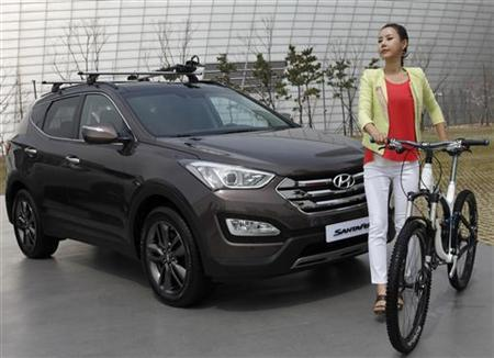 A model poses next to a Hyundai Motor's Santa Fe during an unveiling event of the car in Incheon, west of Seoul April 19, 2012. REUTERS/Lee Jae-Won