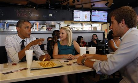 U.S. President Barack Obama reaches for some fries as he holds a round table with first time voters at OMG Burger in Miami, Florida September 20, 2012. Sitting with Obama are University of Miami students Emily Young (C) and Maximo Sole. REUTERS/Kevin Lamarque