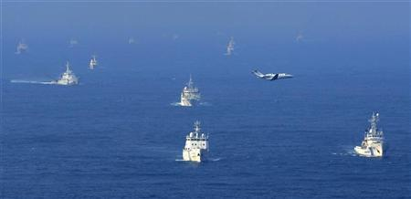 An aerial photo from Kyodo News shows Chinese ocean surveillance, fishery patrol ships and a Japan Coast Guard patrol ship (R and 2nd L) sailing about 27 km (17 miles) west from a group of disputed islands, known as Senkaku in Japan and Diaoyu in China, in the East China Sea in this picture taken by Kyodo September 18, 2012. Mandatory credit REUTERS/Kyodo