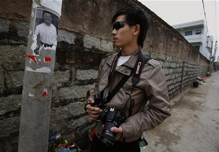Village activist Zhang Jianxing poses in front of a photo of the late village leader Xue Jinbo in Wukan in China's Guangdong province March 3, 2012. REUTERS/Bobby Yip