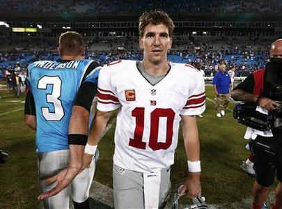 New York Giants quarterback Eli Manning walks on after shaking hands with backup Carolina Panthers quarterback Derek Anderson (L) during a NFL football game in Charlotte, North Carolina September 20, 2012. REUTERS/Chris Keane