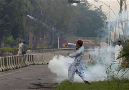 A supporter throws a teargas canister, which was earlier thrown by police, during clashes along a road which leads to the U.S. embassy in Islamabad September 20, 2012. REUTERS/Faisal Mahmood