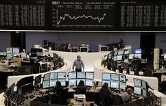 Traders are pictured at their desks in front of the DAX board at the Frankfurt stock exchange September 20, 2012. REUTERS/Remote/Lizza May David
