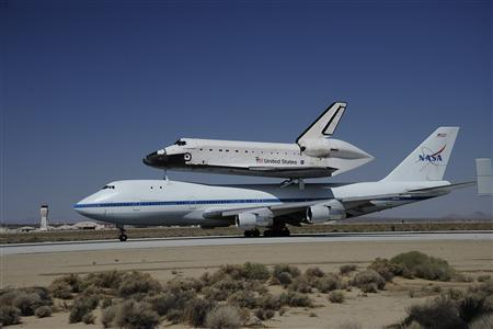 The space shuttle Endeavour, carried piggyback atop a Boeing 747 jumbo jet, comes in for its landing at at Edwards Air Force Base in California, September 20, 2012, after a cross-country trip to Los Angeles to begin its final mission as a museum exhibit. REUTERS/Gene Blevins