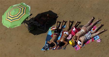 People sunbathe on Regla beach in Chipiona, near the southern Spanish city of Cadiz, August 1, 2010. REUTERS/Javier Barbancho