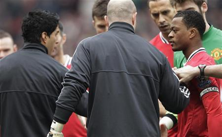 Manchester United's Patrice Evra (R) reacts after Liverpool's Luis Suarez (L) ignored his handshake before their Premier League match at Old Trafford in Manchester, northern England, February 11, 2012. REUTERS/Darren Staples