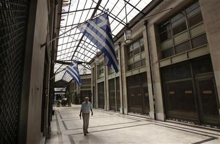 Greek flags are seen as a man walks inside an arcade with closed shops and ''for rent'' signs on them in central Athens August 22, 2012. REUTERS/John Kolesidis
