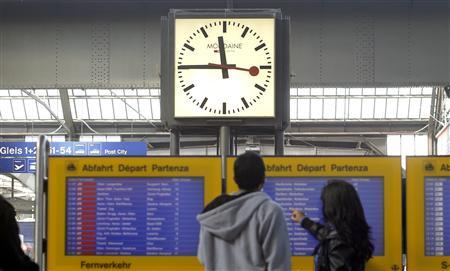 A couple stands in front of a station clock as they check the departure times of trains at the central railway station in Zurich September 21, 2012. REUTERS/Arnd Wiegmann