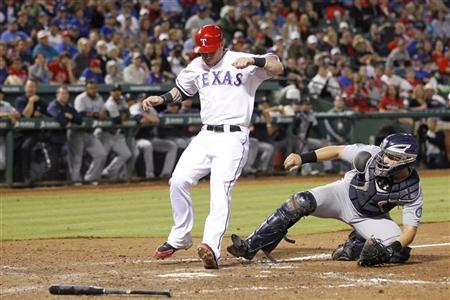 Texas Rangers Josh Hamilton scores as Seattle Mariners catcher Jesus Montero is unable to make the tag in time in the eighth inning of their MLB American League baseball game in Arlington, Texas September 14, 2012. REUTERS/Mike Stone