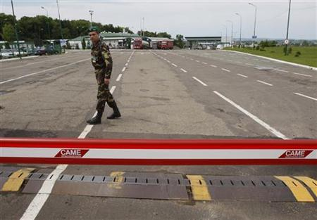 An Ukrainian border guard waits for vehicles at a checkpoint in Shegyni, at the Ukrainian-Polish border June 15, 2009. REUTERS/Gleb Garanich