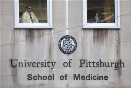 Two people wait to leave the University of Pittsburgh School of Medicine after the area was locked down by police due to a shooting at the Western Psychiatric Institute and Clinic of University of Pittsburgh Medical Center in Pittsburgh, Pennsylvania March 8, 2012. REUTERS/ Jason Cohn