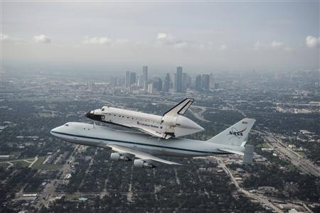 The space shuttle Endeavour, atop NASA's Shuttle Carrier Aircraft, flies over Houston, Texas in this September 19, 2012 NASA handout photo. The SCA, a modified 747 jetliner is flying Endeavour to Los Angeles where it will be placed on public display at the California Science Center. This is the final ferry flight scheduled in the Space Shuttle Program era. REUTERS-Sheir Locke-NASA-Handout