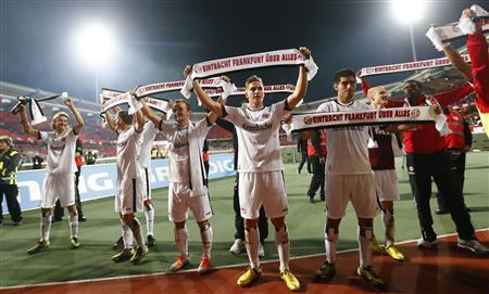 Eintracht Frankfurt's players celebrate with scarves reading after their German first division Bundesliga soccer match against FC Nuremberg in Nuremberg, September 21, 2012. Frankfurt won the match 2-1 and took the lead in Germany's Bundesliga. The scarves read, ''Eintracht Frankfurt on top of everything''. REUTERS/Kai Pfaffenbach