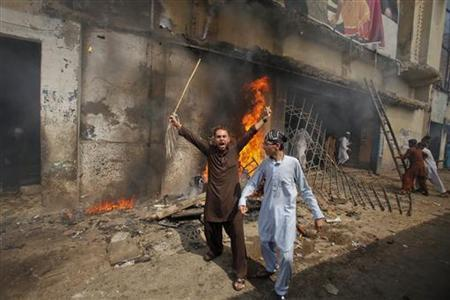 A protester holds a stick as he shouts anti-American slogans in front of a burning cinema during an anti-U.S. protest rally to mark the ''Day of Love'' in Peshawar September 21, 2012. Demonstrators clashed with police in the Pakistani city of Peshawar on Friday as anger over insults to the Prophet Mohammad boiled over despite calls from political and religious leaders across the Muslim world for peaceful protest. REUTERS/Fayaz Aziz