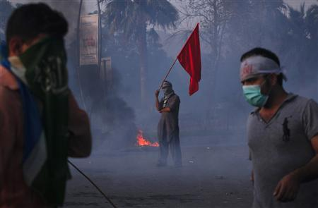 A protester holds a red flag as he stands amongst teargas smoke during an anti-American protest rally to mark the ''Day of Love'' in Islamabad September 21, 2012. Pakistan has declared Friday a ''Day of Love for the Prophet Mohammad''. Critics of the unpopular government said it was pandering to Islamist parties. Protesters took to the streets of the Pakistani city of Peshawar, an old frontier town on the main road to Afghanistan, and torched two cinemas and clashed with riot police who tried to disperse them with teargas. REUTERS/Akhtar Soomro