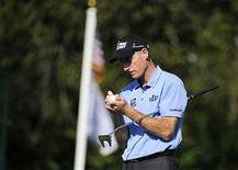 Jim Furyk of the U.S. signs his golf ball after putting out on hole 16 during the second round of the Tour Championship golf tournament at the East Lake Golf Club in Atlanta, Georgia, September 21, 2012. REUTERS/David Tulis