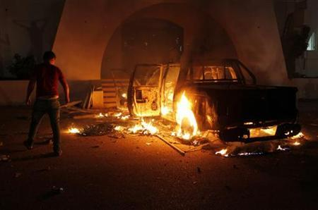 A demonstrator stands next to a burning car which the demonstrators set alight and said was full of ammunition as they stormed the headquarters of the Islamist Ansar al-Sharia militia group in Benghazi September 21, 2012. Pro-government demonstrators stormed the headquarters on Friday and evicted fighters from the site in a sweep of militia bases in Benghazi, Reuters witnesses said. REUTERS/Asmaa Waguih