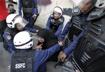 Riot policewomen arrest an anti-government protester during a demonstration in capital Manama, September 21, 2012. REUTERS/Hamad I Mohammed