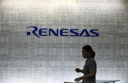 A receptionist passes by a logo of Renesas Electronics Corp at the company's headquarters in Tokyo July 3, 2012. Japan's loss-making Renesas Electronics Corp said on Tuesday it will seek to cut around 5,000 jobs through voluntary redundancies by the end of October. REUTERS/Yuriko Nakao