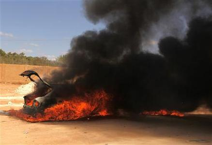 A car burns after it was set on fire by demonstrators who attacked the base of the Rafalla al-Sihati brigade, part of the Libyan army, in Benghazi city September 22, 2012. REUTERS/Asmaa Waguih