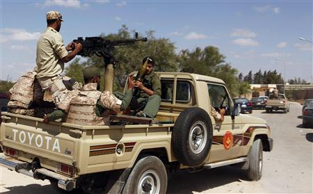 Members of the National Army ride in their vehicles as they enter the gates of pro-government Rafalla al-Sihati brigade after demonstrators attacked the brigade's base in Benghazi city September 22, 2012. REUTERS/Asmaa Waguih