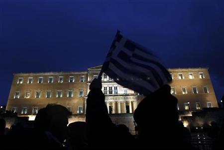 A protester holds up a Greek flag during an anti-austerity demonstration in front of the parliament in Athens February 22, 2012. REUTERS/Yannis Behrakis