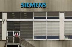 A man stands in front of a building of Siemens Schweiz AG Building Technologies Group, a Swiss unit of German Siemens AG in the central Swiss town of Zug September 20, 2012. REUTERS/Arnd Wiegmann