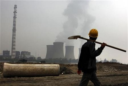 A coal-burning power station can be seen behind a migrant worker as he walks carrying his shovel on the construction site of a water canal, being built in a dried-up river bed located on the outskirts of Beijing October 22, 2010. REUTERS/David Gray