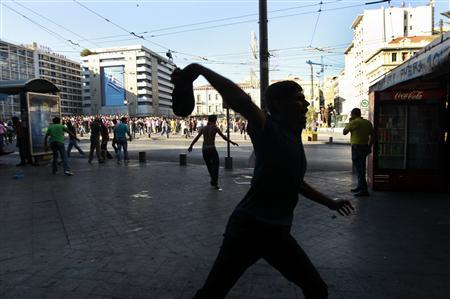 A Muslim protester throws a shoe at policemen during a rally in central Athens September 23, 2012. REUTERS/John Kolesidis