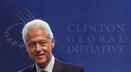 Former U.S. President Bill Clinton stands in front of the logo of the Clinton Global Initiative 2012 (CGI) during the first day of the CGI in New York, September 23, 2012. REUTERS/Lucas Jackson