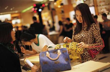 A woman shops in a Louis Vuitton store in downtown Shanghai September 7, 2012. REUTERS/ Carlos Barria