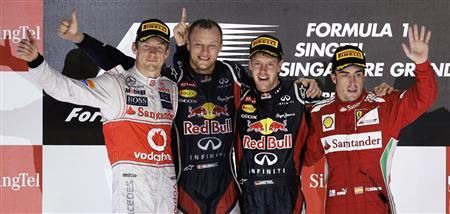 McLaren Formula One driver Jenson Button of Britain (L), Red Bull Formula One driver Sebastian Vettel of Germany (2nd R), Vettel's front end engineer Ole Schack of Denmark and Ferrari Formula One driver Fernando Alonso of Spain (R) celebrate on the podium after the Singapore F1 Grand Prix at the Marina Bay street circuit in Singapore September 23, 2012. REUTERS/Tim Chong