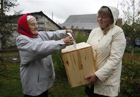 A woman casts her vote into a portable ballot box during the parliamentary elections near her house in the village of Slobodschina, about 30 km (19 miles) northeast of Minsk, September 23, 2012. Belarus voted on Sunday in a parliamentary election which was likely to reinforce hardline President Alexander Lukashenko's grip on the small former-Soviet country despite a boycott call from the dispirited opposition. REUTERS/Vladimir Nikolsky