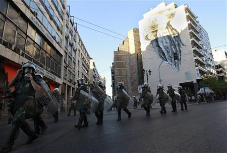Riot police walk in front of a building with graffiti during a rally by Muslim protesters in central Athens September 23, 2012. REUTERS/John Kolesidis