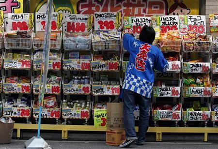 An employee wearing a Japanese happi coat with letters reading, ''big sale,'' works at a drug store in Tokyo March 8, 2012. JREUTERS/Yuriko Nakao