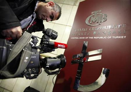 A cameraman films the new symbol of Turkish Lira displayed in a hall in Central Bank headquarters in Ankara March 1, 2012. REUTERS/Umit Bektas