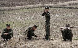 Armed North Korean soldiers joke with Chinese tourists as they keep guard at Hwanggumpyong Island, near the North Korean town of Sinuiju and the Chinese border city of Dandong, May 1, 2012. REUTERS/Jacky Chen (NORTH KOREA - Tags: MILITARY POLITICS SOCIETY TPX IMAGES OF THE DAY)